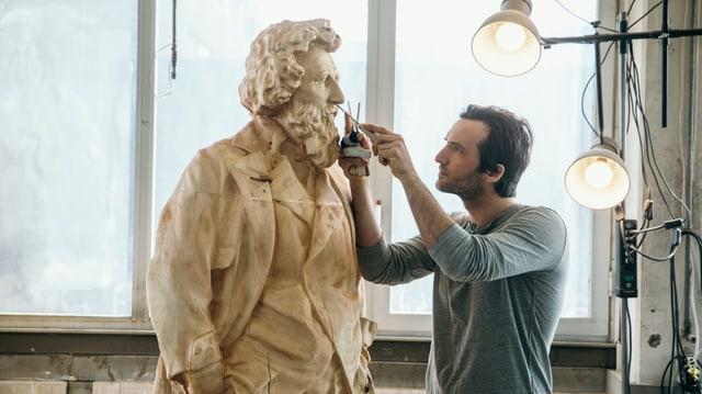 L'artist Inigo Gheyselinck lavura vid la statua da l'artist Segantini.
