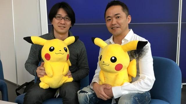 Shigeru Ohmori (links im Bild) und Junichi Masuda halten beide eine Pikachu-Plüschpuppe auf den Knien.