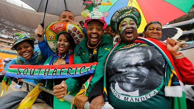 Mehrere Afrikaner, die T-Shirts mit dem Aufdruck von Mandela und Fahnen auf sich tragen