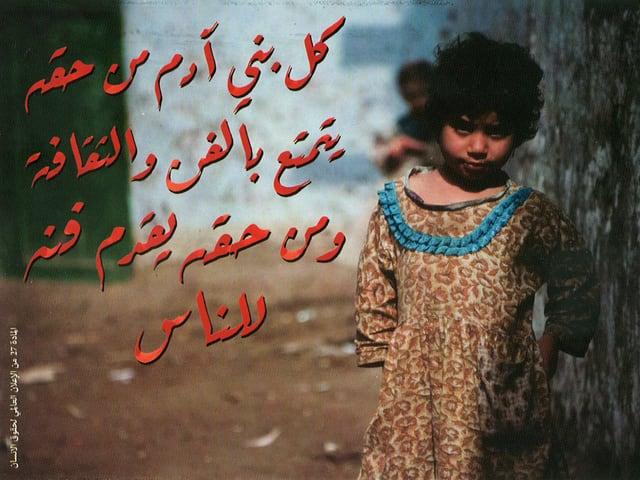 Ein kleines Mädchen steht schüchtern neben einem Baum und schaut in die Kamera. Neben ihr steht in arabischer Schrift der Postkarten-Spruch.