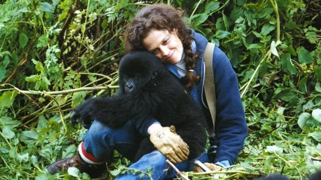 Schauspielerin Sigourney Weaver schmust in einer Drehpause mit einem jungen Gorilla.