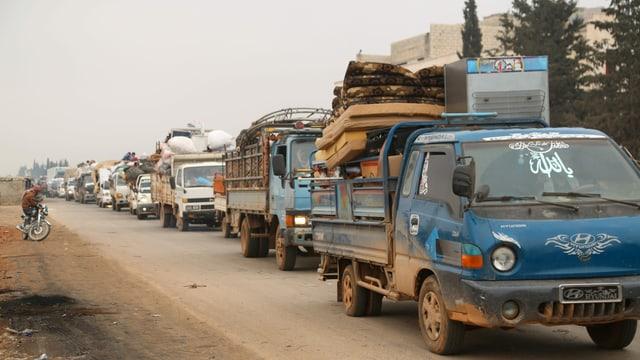 Lastwagen transportieren die Habseligkeiten von Menschen.