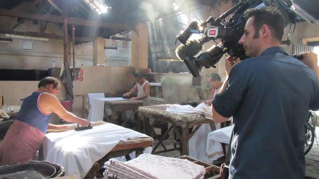 Kameramann filmt Arbeiter in indonesischer Batik-Fabrik.