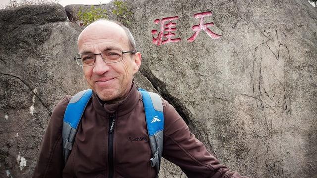 Ein Mann steht vor einem Stein mit chinesischen Schriftzeichen und einem Porträt einer Frau