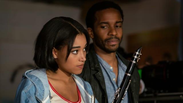 eine junge Frau mit einem Mann im Hintergrund, der eine Klarinette hält