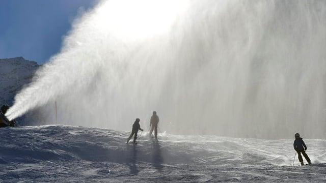 Drei Skifahrer im Nebel einer Schneekanone