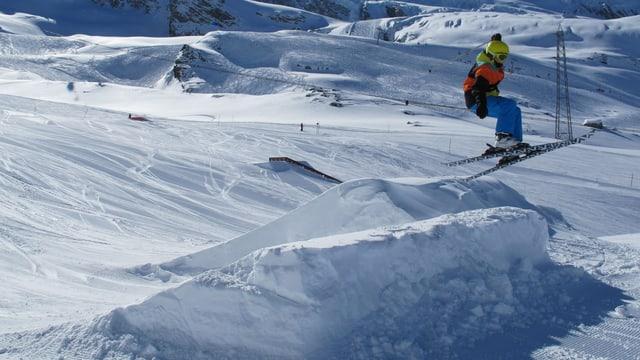 Ein Skifahrer springt über die Schanze.