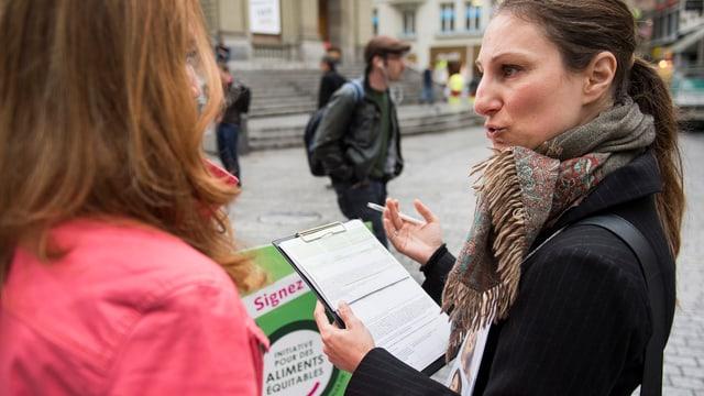 Eine Frau mit einem Unterschriftenbogen in der Hand spricht mit einer anderen Frau.