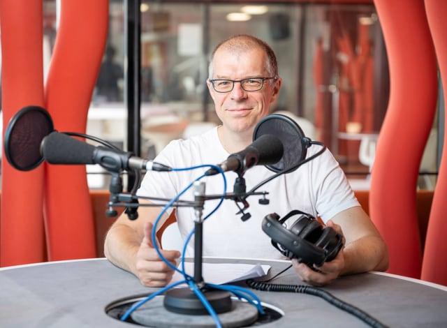 Markus Gasser sitzt in einem Sendestudio vor einem Mikrophon.