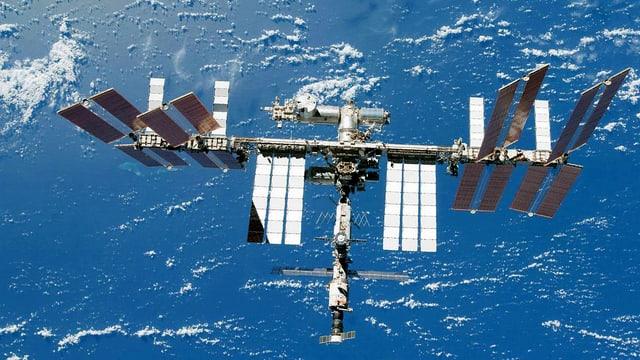 Blick auf die Raumstation ISS. Im Hintergrund das helle Blau der Erdkugel mit kleinen Wölklein.
