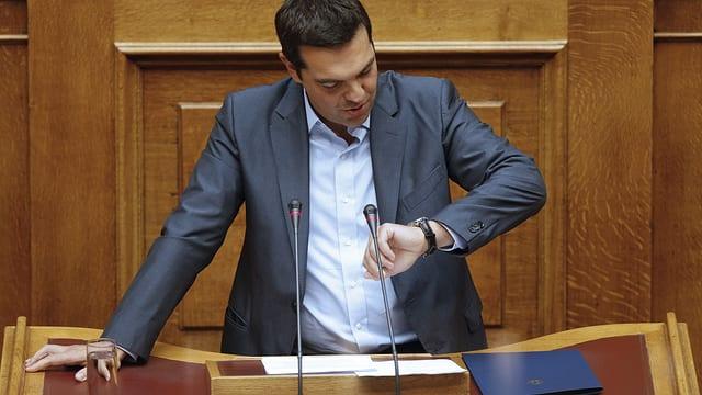 Griechenlands Ministerpräsident Alexis Tsipras schaut am Rednerpult des Parlaments auf seine Uhr.