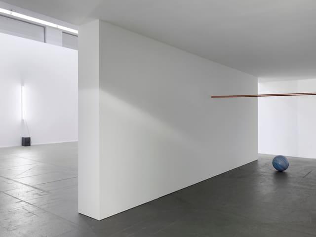Ein fast leerer Museumsraum: auf dem Boden eine blaue Steinkugel und darüber eine goldene Stange.