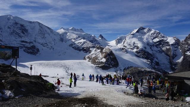 Davos ves'ins il Palü cuvert en naiv cul glatscher, dasper ulteriuras muntgonas ed a dretga il Bernina cul Bianco Grat. Davant ves'ins glieud che stà enturn maisas e giauda in apero.
