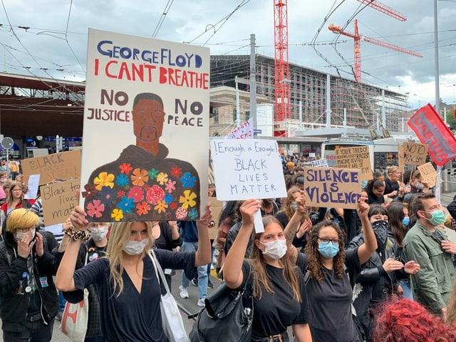 Kundgebungsteilnehmer halten Plakate hoch