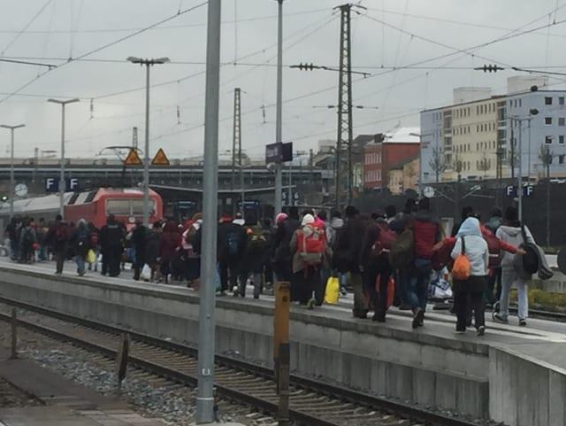 Dutzende Menschen auf einem Bahnhof-Perron.