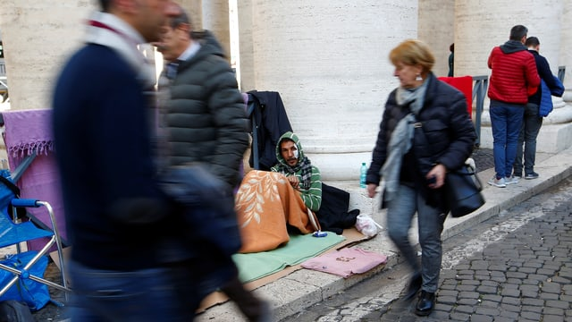 Menschen gehen an Obdachlosen auf dem Petersplatz vorbei