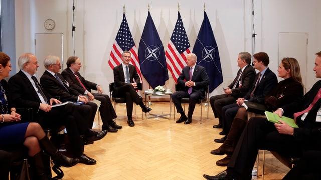 Männer auf Stühlen in einem Kreis.