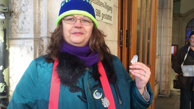 Eine Frau hält eine Basler «Fasnachts-Blagedde» beim Bahnhofseingang.