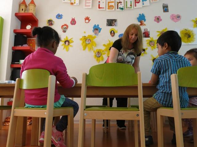 Kindern aus verschiedenen Ländern in der Spielgruppe am Tisch.