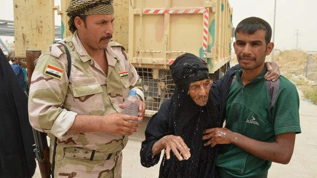 Ein irakischer Soldat gibt einer alten Frau Wasser.
