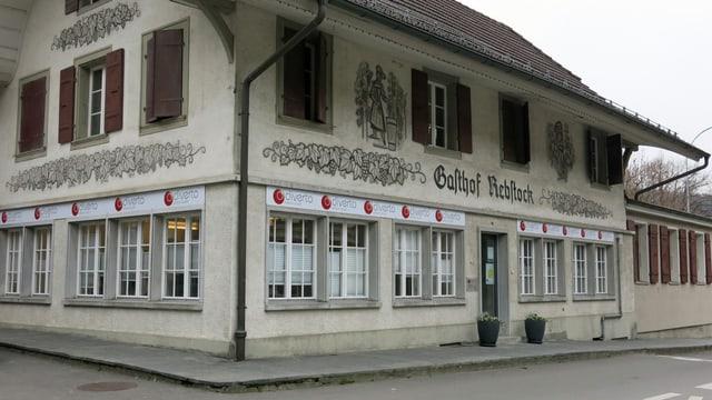 Gebäude mit Schriftzug «Gasthof Rebstock» und neuen Büro-Logos.