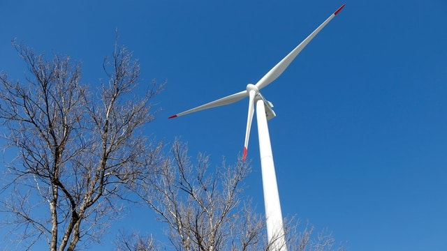 Ein Windrad vor einem blauen Himmel