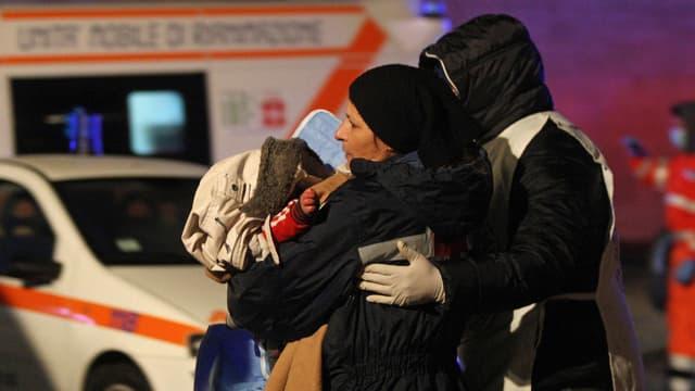 Eine Frau mit einem Baby im Arm wird von einem Helfer zu einer Ambulanz begleitet.