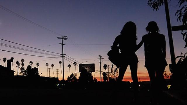 Silhouetten von zwei Frauen zeichnen sich gegen den Himmel ab, wo gerade die Sonne untergeht.