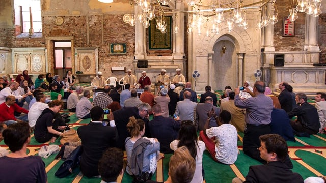 Besucher der Biennale auf dem Gebetsteppich einer alten Kirche, die zu einer Moschee umfunktioniert wurde.