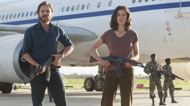Daniel Brühl posiert mit der falschen Deutschen (Rosamund Pike) vor dem entführten Flugzeug.