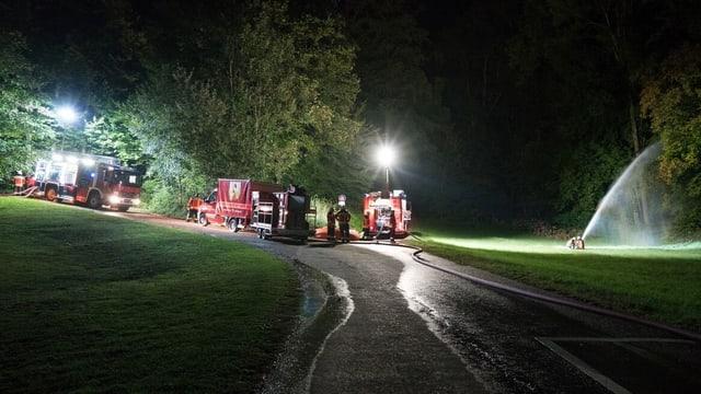 Feuerwehrautos bei Nacht. Daneben eine Wasserspritze.