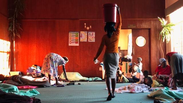 Frauen und Kinder haben ihr Lager auf dem Hotelboden aufgeschlagen. Ein Frau trägt in der Mitte einen Kessel auf dem Kopf.