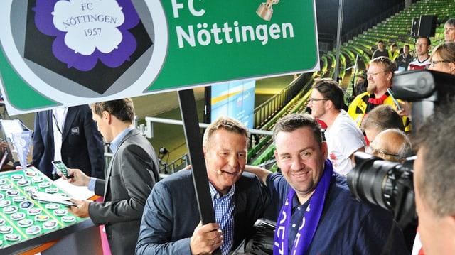 Vorstandsboss Dirk Steidl und Ex-Profi Karlheinz Förster halten ein Schild mit der Aufschrift «FC Nöttingen» in die Höhe.