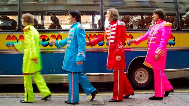 Vier Fake-Beatles in Abbey-Road-Formation vor einem einem Bus.
