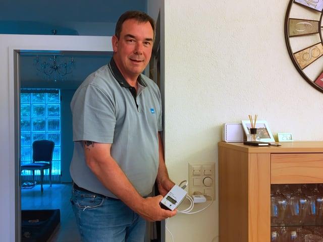 Der Stromdetektiv hat sein Messgerät in eine Steckdose eingesteckt.