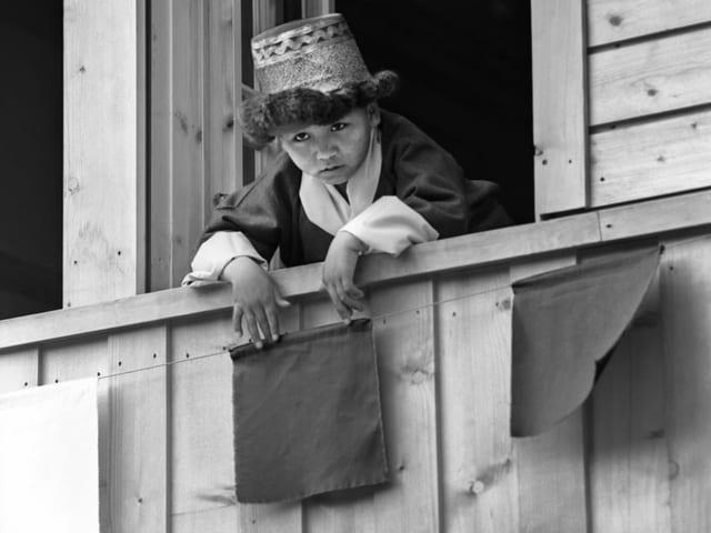 Kleiner Jung mit tibetischem Kopfschmuck schaut etwas ängstlich aus dem Fenster.
