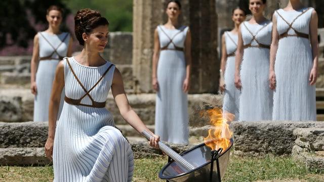 Ad Olimpia envida ina ballerina greca tradiziunala la flomma.