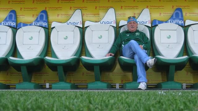 Franz Malara sitzt auf der Trainerbank im Stadion mit grüner FCSG Jacke und Sonnenbrille auf dem Kopf