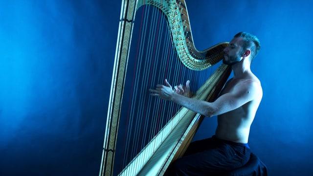 Ein junger Mann spielt Harfe. Er trägt kein Oberteil.