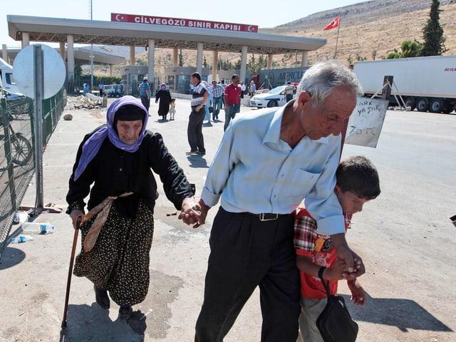 Zwei ältere Personen und ein Junge passieren die türkische Grenze