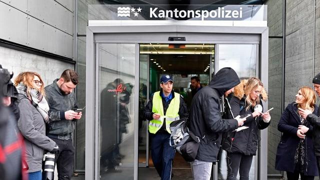 Persunas da medias davant l'isch da la polizia chantunala da l'Argovia a Schafisheim