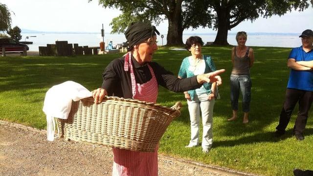 Eine ältere Frau mit Kopftuch und Schürze trägt einen Wäschekorb.