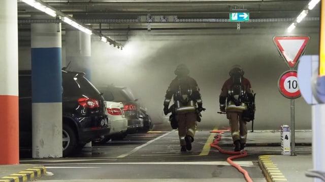 Zwei Feuerwehrleute in verrauchter Tiefgarage.