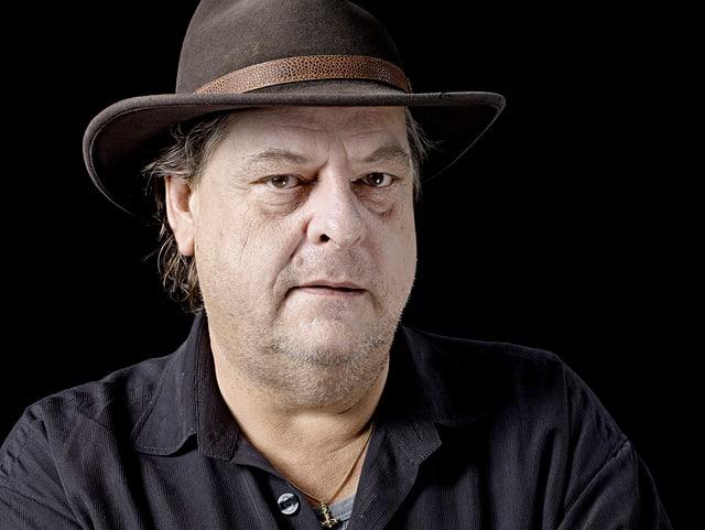 Ein Porträt von Endo Anaconda. Er trägt ein schwarzes Hemd und einen Hut.