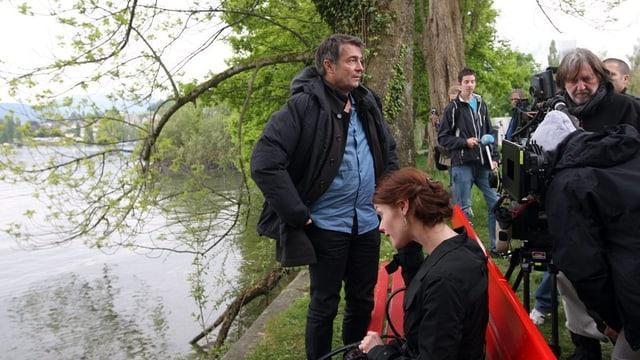 Verschiedene Menschen mit Kameras an einem Ufer.