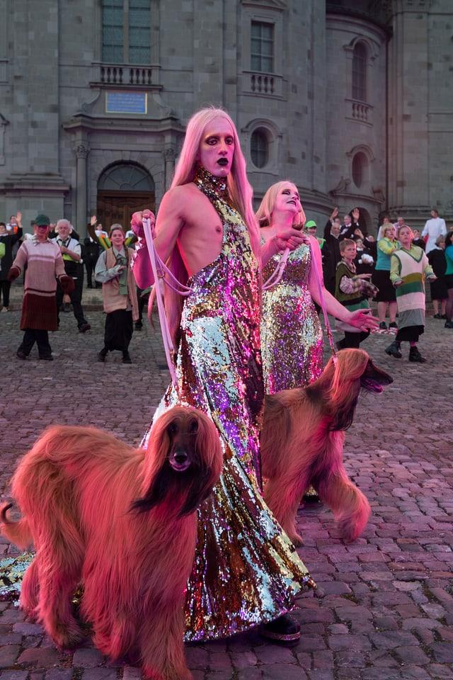 Welttheater: Zwei Darsteller mit langhaarigen, grossen Hunden. Alle pink eingefärbt.
