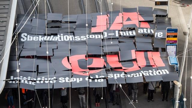 Demonstranten halten ein Plakat mit der Aufschrift «Ja Spekulationsstopp-Initiative»