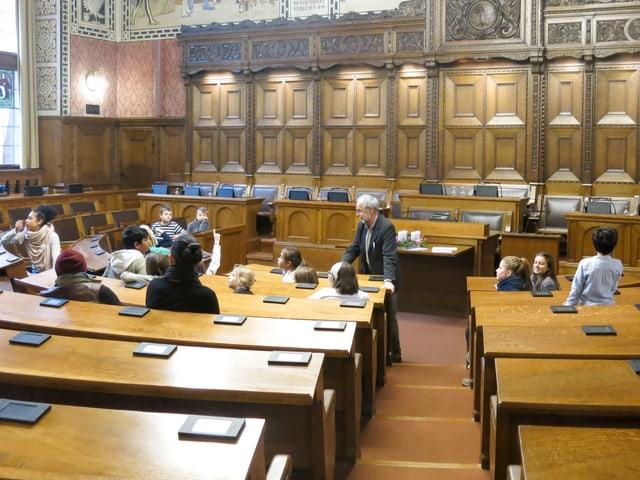 Im Saal des Grossen Rates im Rathaus sitzen Kinder aus demGotthelfschulhaus. Vor ihnen Osi Inglin, der die Bilder an den Wänden erklärt.