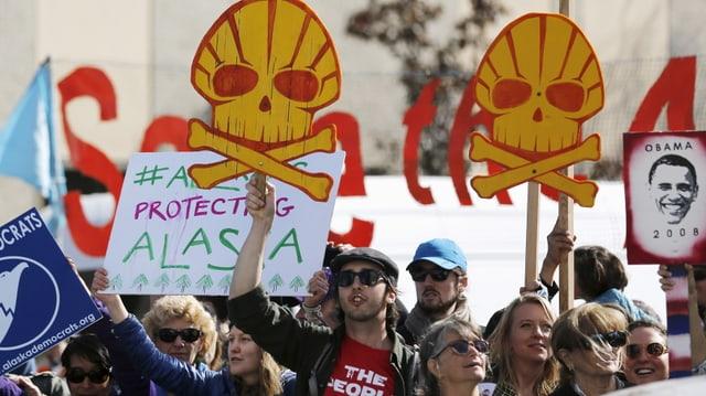 Protestierende halten Schilder, die das Shell-Logo als Totenkopf zeigen.