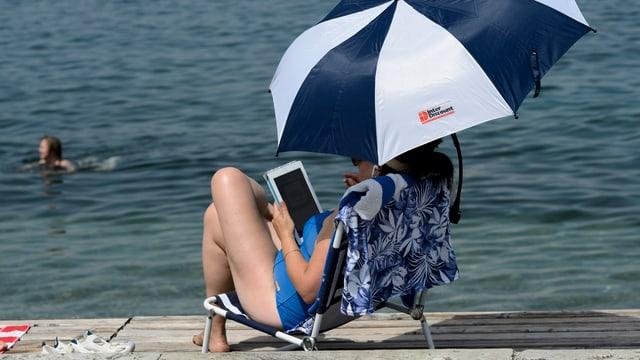 Frau sitzt unter einem Sonnenschirm und hält ein Tablet in der Hand.